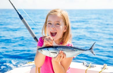 Girl holding a fish that she just caught